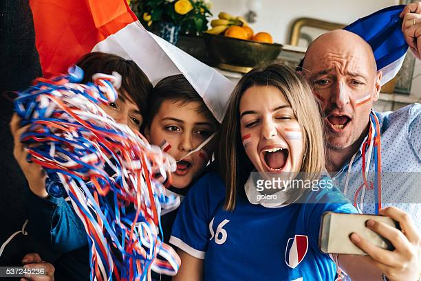 french family watching soccer match on smartphone