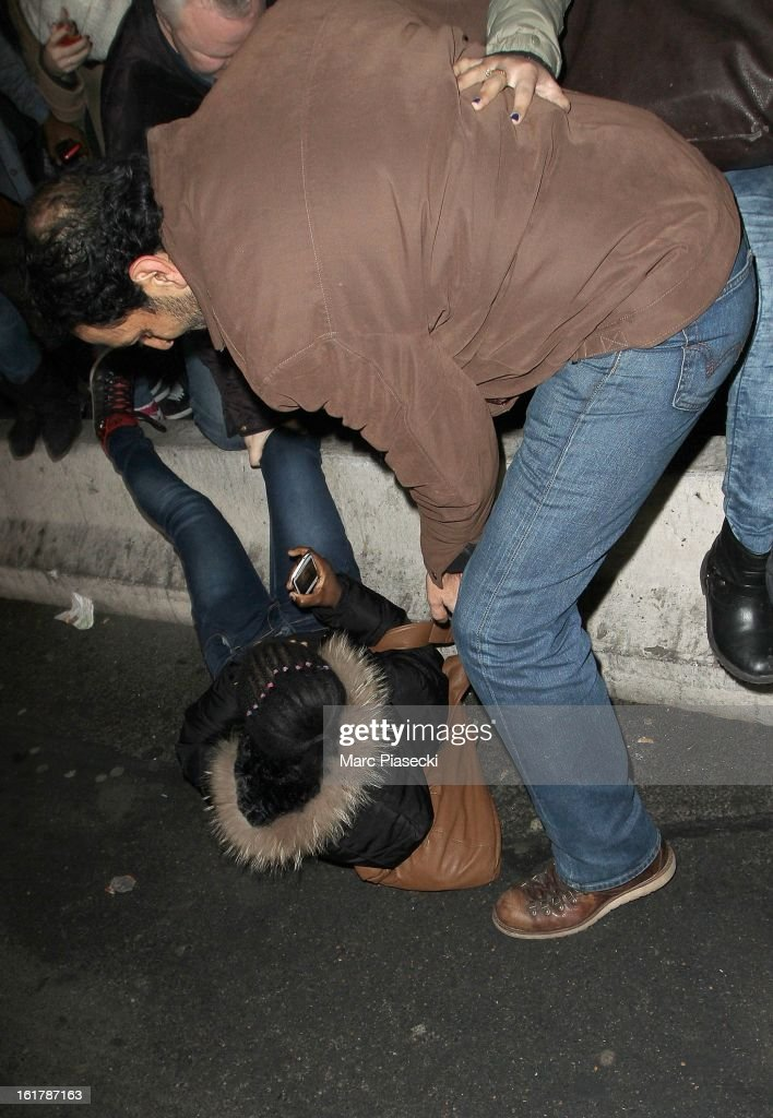 A french fan falls in front of actresses Ashley Benson and Selena Gomez arrive at Roissy airport on February 16, 2013 in Paris, France.
