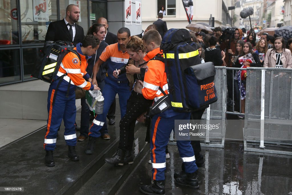 A french fan is assisted by the parisian rescuers as singer Miley Cyrus is seen leaving the 'NRJ' radio station on September 9, 2013 in Paris, France.
