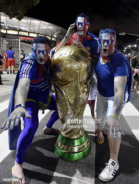 French fans celebrate with a giant mockup of the World Cup trophy after France won a Group E football match between Switzerland and France at the...