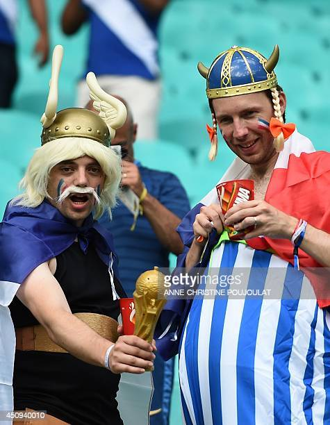 French fans dressed up as the French cartoon characters Asterix and Obelix hold a replica of a FIFA World Cup trophy as they wait for the kickoff of...