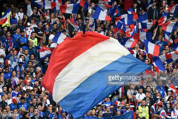 TOPSHOT French fans unfurl the national flag as they wait for the start of the Euro 2016 group A football match between Switzerland and France at the...