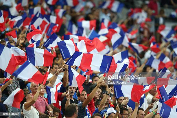 French fans wave their flags during the International match between France and England at Stade de France on August 22 2015 in Paris France