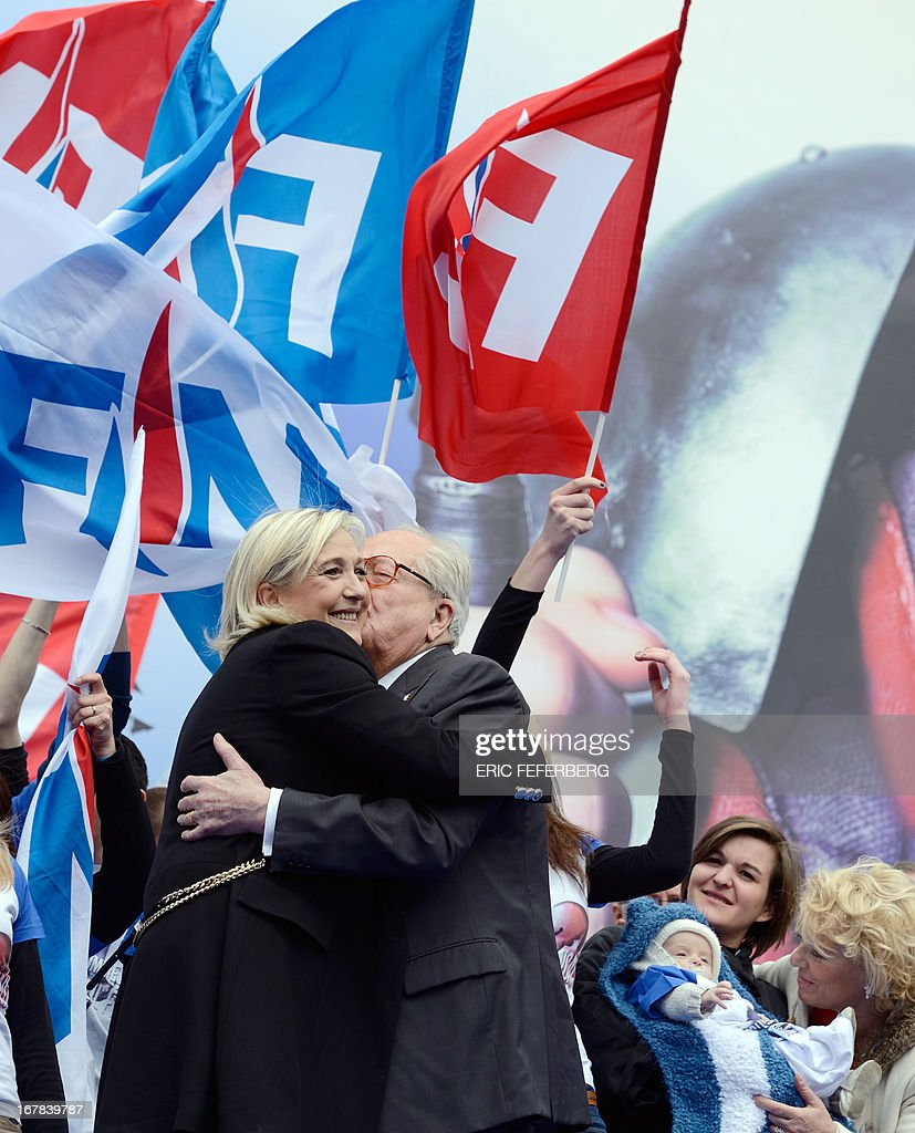 French far right Front National (FN) party president Marine Le Pen (front, L) embraces her father, FN honorary president Jean-Marie Le Pen during the party's annual celebrations of Joan of Arc on May 1, 2013 at Paris' Opera square.