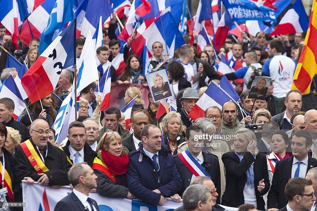 French far right party Front National (FN) vice-president Florian Philippot, president Marine Le Pen, local elected Nicolas Bay, general secretary Steeve Briois, march towards Paris' Opera square during the party's annual celebrations of Joan of Arc on May 1, 2013.