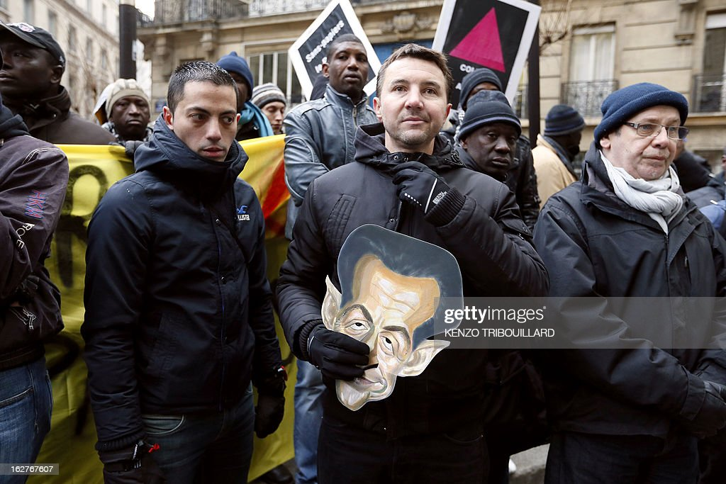 French far-left anti-capitalist NPA party's member and former presidential candidate, Olivier Besancenot (C) holds a Nicolas Sarkozy mask as he takes part with illegal immigrants and militants to a demonstration to call for the legalization of all undocumented immigrants in front of the Interior ministry on February 26, 2013 in Paris. AFP PHOTO KENZO TRIBOUILLARD