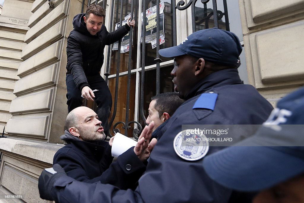 French far-left anti-capitalist NPA party's member and former presidential candidate, Olivier Besancenot (up) gestures as he takes part with illegal immigrants and militants to a demonstration to call for the legalization of all undocumented immigrants in front of the Interior ministry on February 26, 2013 in Paris. AFP PHOTO KENZO TRIBOUILLARD