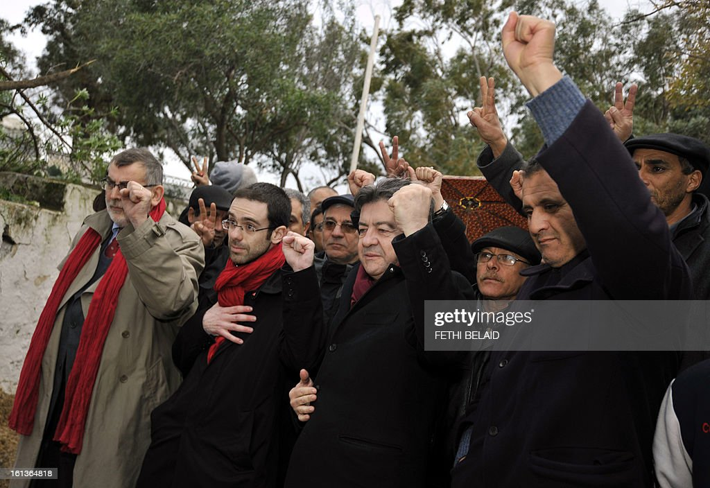 French far-left Parti de Gauche (PG) party leader, Jean-Luc Melenchon (3rd L) holds his fist up at the grave of assassinated opposition leader Chokri Belaid in the el-Jellaz cemetery, on February 10, 2013, in the capital Tunis. Tunisian Prime Minister Hamadi Jebali's gamble on forming a new government in defiance of his own Islamist party after the assassination of Belaid has left Tunisia in political limbo. AFP PHOTO / FETHI BELAID
