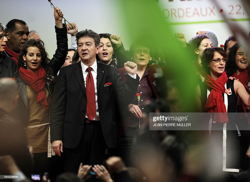 French far-left Parti de Gauche (PG) party leader, Jean-Luc Melenchon (C) next to supporters ,sings the national anthem La Marseillaise at the end of the 3rd congress of the PG in Bordeaux on March 24, 2013. AFP PHOTO JEAN-PIERRE MULLER