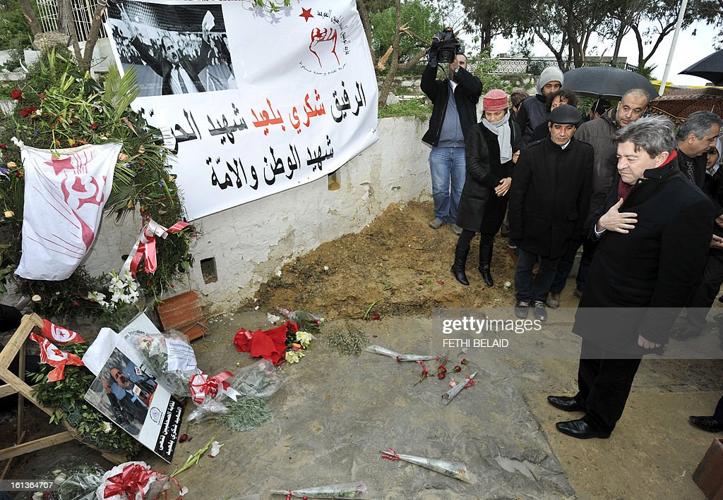 French far-left Parti de Gauche (PG) party leader, Jean-Luc Melenchon (R) pays his respect at the grave of assassinated opposition leader Chokri Belaid in the el-Jellaz cemetery, on February 10, 2013, in the capital Tunis. Tunisian Prime Minister Hamadi Jebali's gamble on forming a new government in defiance of his own Islamist party after the assassination of Belaid has left Tunisia in political limbo.