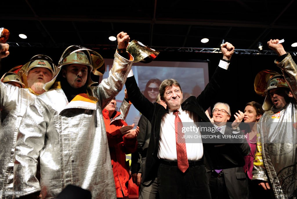 French far-left Parti de Gauche (PG) party's leader Jean-Luc Melenchon (C) raises his fists beside ArcelorMittal unionists, on January 23, 2013 in Metz, eastern France, during a meeting launching the French left-wing Front de Gauche (FG) party's campaign entitled 'Alternative to austerity, it's possible'. AFP PHOTO / JEAN-CHRISTOPHE VERHAEGEN