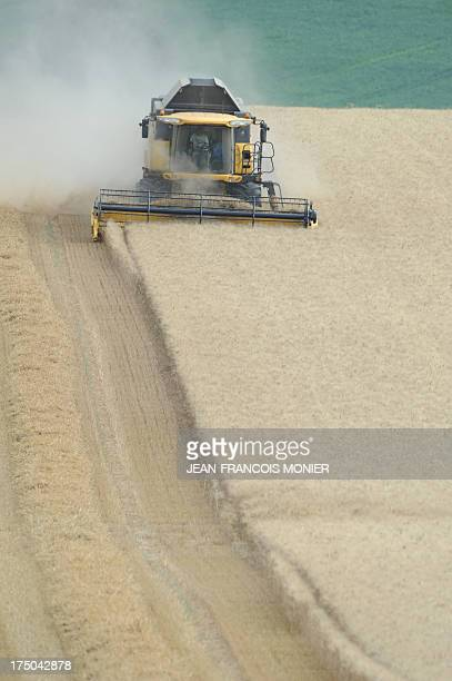 French farmer harvests a wheat field with a combine harvester late on July 25 in CivraysurEsves central France Due to weather conditions the harvests...