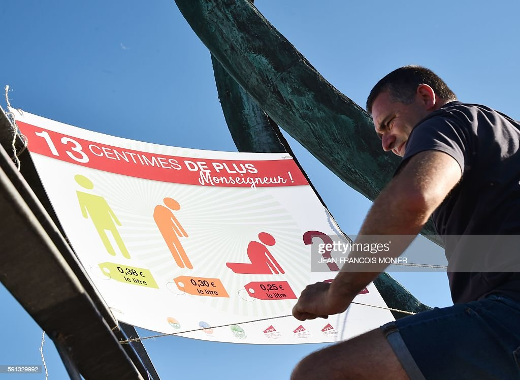 A French farmer installs a banner reading '13 cents more Monseigneur' on August 22 2016 in front of the Lactalis headquarters Group in Change near...