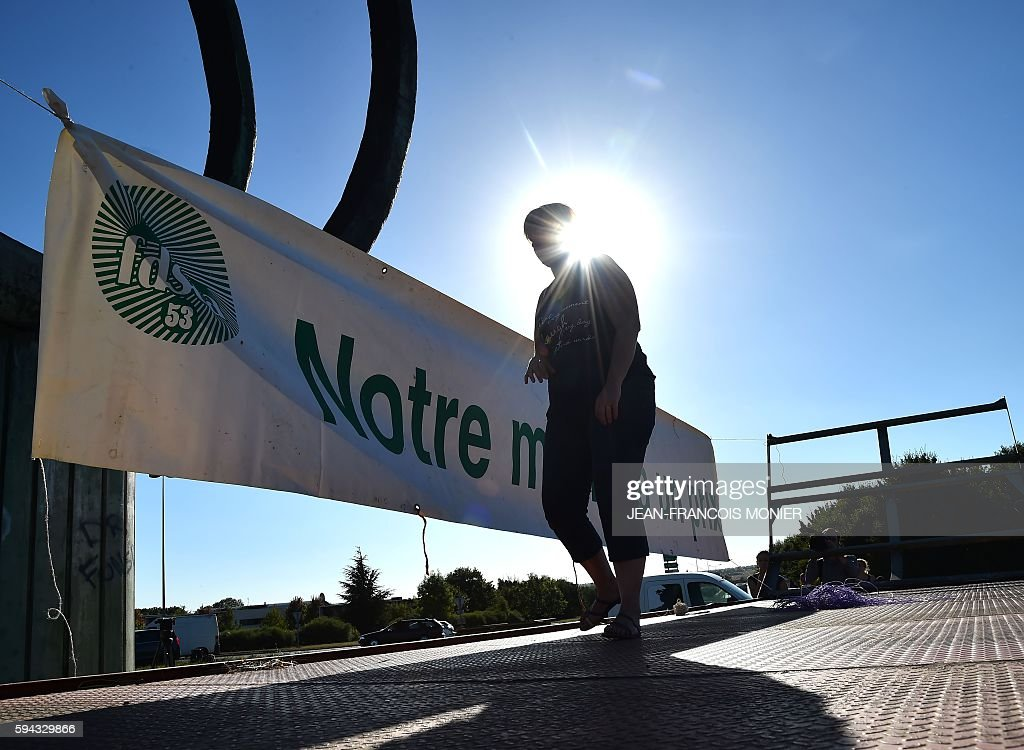 A French farmer installs a banner reading 'Our business has a price' on August 22 2016 in front of the Lactalis headquarters Group in Change near...