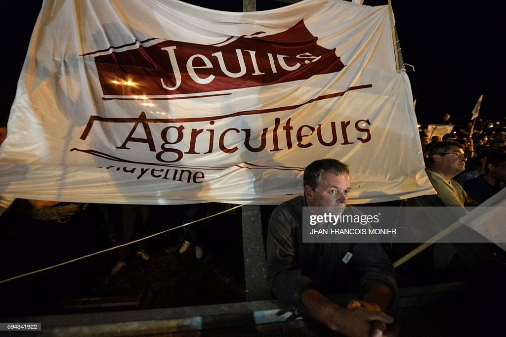 A french farmer seen in front of a banner reading 'Young farmers' listens to the President of the French Departmental Federation of Farmers Unions...
