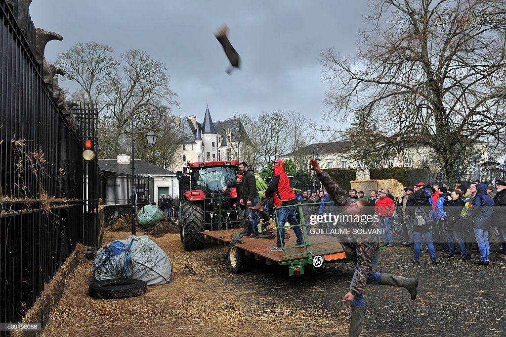 A French farmer throws a boot over the gate of the prefecture of Indre, on February 9, 2016, in Chateauroux, central France, during a protest against the falling prices of agricultural products. / AFP / GUILLAUME SOUVANT