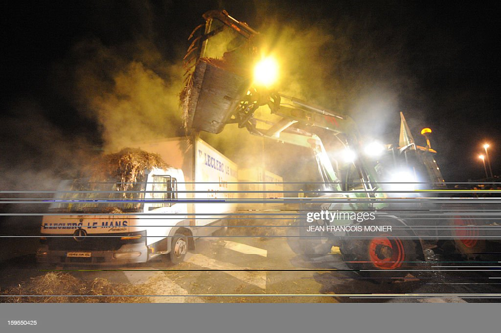 A French farmer uses a tractor (R) to offload manure in front of a Leclerk supermarket truck (L) during a demonstration of French farmers in Le Mans on January 16, 2013.