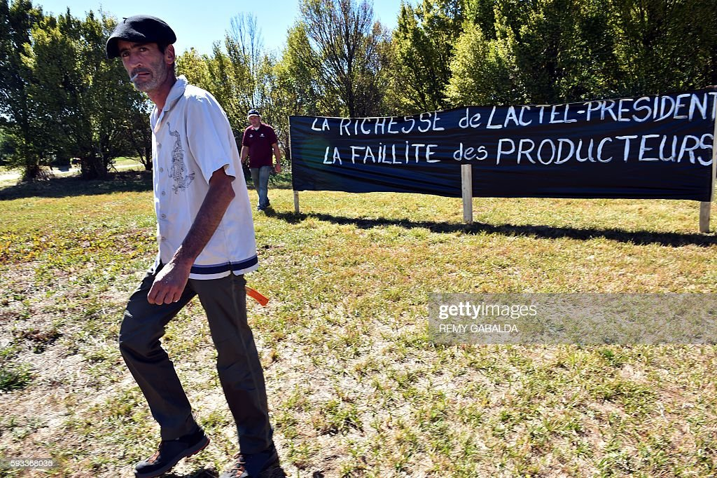A French farmer walks past a banner reading 'The wealth of LactelPresident the bankruptcy of the farmers' after installing it by a factory of the...