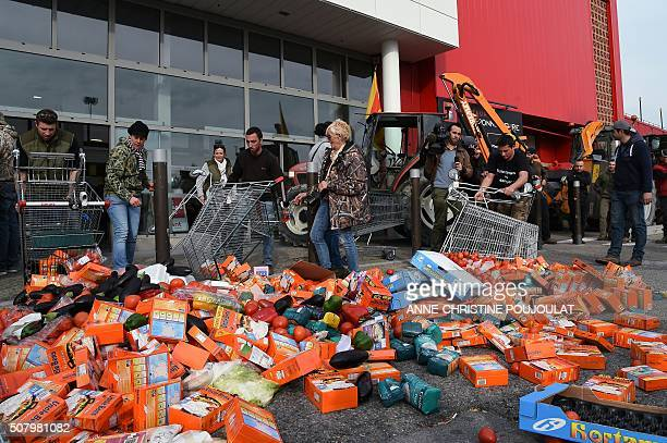 French farmers and rice farmers throw vegetables and packets of rice on the ground in front of a supermarket on February 2 2016 in SalondeProvence...