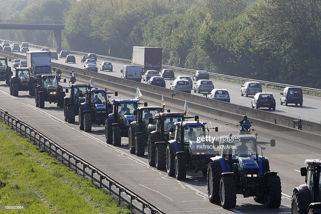 French farmers drive their tractors on a highway near Noisy-Le-Grand, east of Paris, on April 27, 2010 before demonstrating in Paris against wages cut and to denounce the European Farm Policy. The demonstration headed by grain farmers was called by 14 regional unions and backed by the National Farmers union (FNSEA).