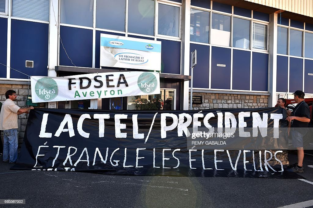 French farmers hold a banner reading 'Lactel / President strangles the farmers' before hanging it on the frontage of of a factory of the French group...