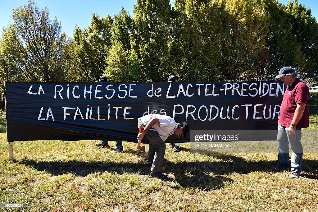 French farmers install a banner reading 'The wealth of LactelPresident the bankruptcy of the farmers' by a factory of the French group Lactalis in...