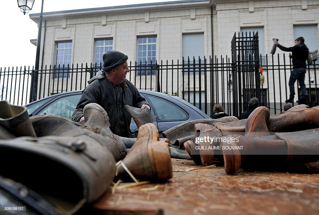 French farmers put boots on the gates of the prefecture of Indre, on February 9, 2016, in Chateauroux, central France, during a protest against the falling prices of agricultural products. / AFP / GUILLAUME SOUVANT