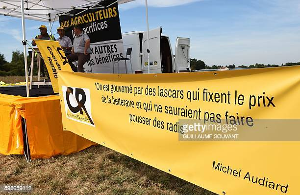 French farmers sit under a tent next to a banner reading a quote of Michel Audiard 'We are governed by shady characters who set the price of...
