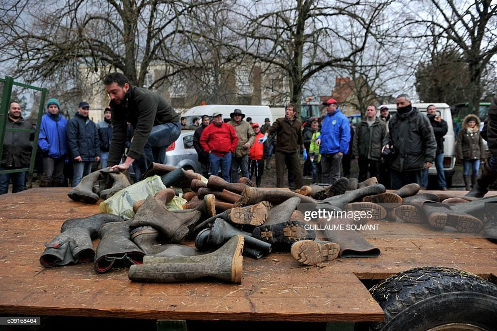 French farmers start to block the access of the prefecture of Indre throwing boots, on February 9, 2016, in Chateauroux, central France, during a protest against the falling prices of agricultural products. / AFP / GUILLAUME SOUVANT