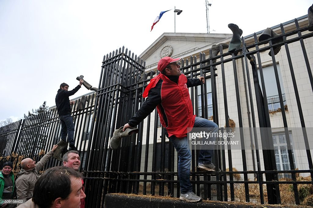 French farmers throw boots over the gate of the prefecture of Indre, on February 9, 2016, in Chateauroux, central France, during a protest against the falling prices of agricultural products. / AFP / GUILLAUME SOUVANT