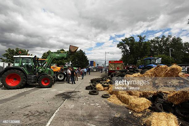 French farmers throws used tyres and hay bales from a truck to form a blockade at the Europe bridge leading over the Rhine between Strasbourg and...