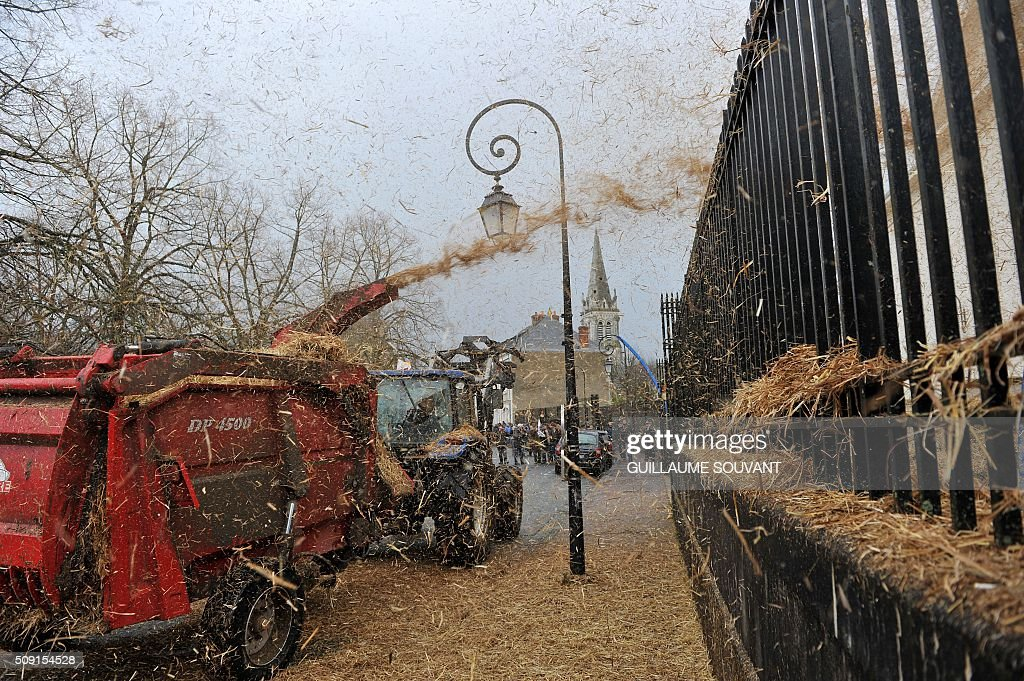 French farmers use a threshing machine to spray straw onto the gates of the Prefecture of the Indre French departement, during a demonstration on February 9, 2016, in Chateauroux, central France, protesting against the falling prices of agricultural products. / AFP / GUILLAUME SOUVANT