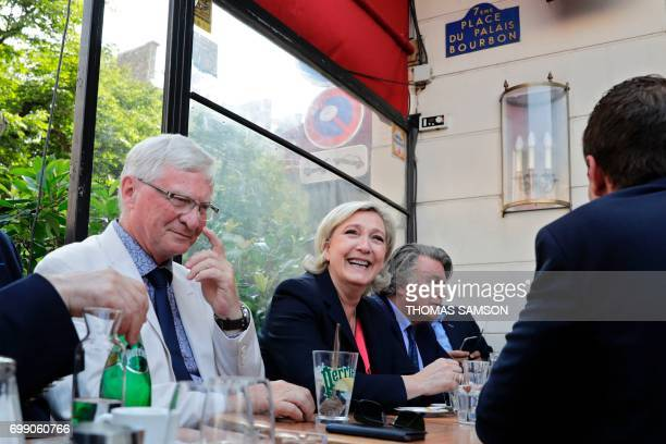 French farrigh Front National party's newly elected Members of Parliament Jose Evrard Marine Le Pen and Gilbert Collard sit in a cafe on June 21 2017...