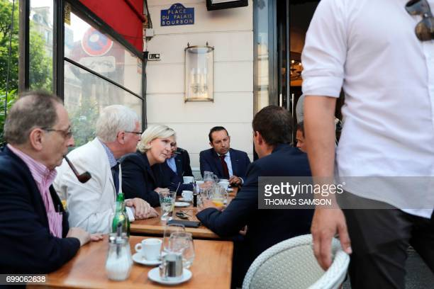 French farrigh Front National party's newly elected Members of Parliament Jose Evrard Marine Le Pen and Sebastien Chenu sit in a cafe on June 21 2017...
