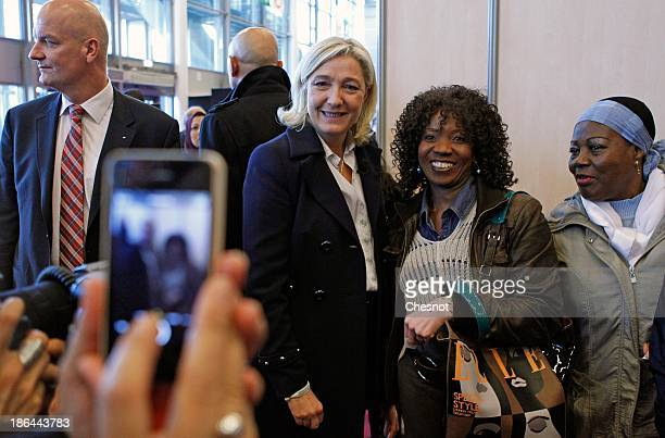 French farright FN party President Marine Le Pen poses with visitors as she visits the chocolate fair at Parc des Expositions Porte de Versailles on...