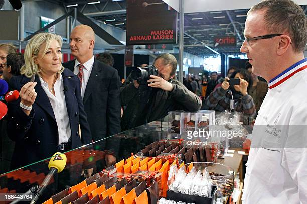 French farright FN party President Marine Le Pen speaks with a chocolate maker as she visits the chocolate fair at Parc des Expositions Porte de...