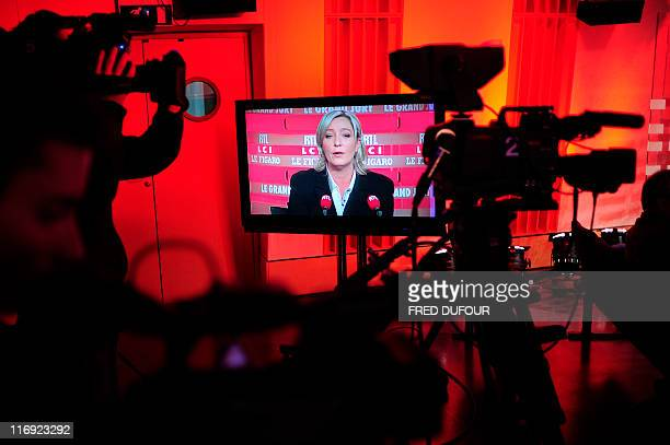 French farright Front national deputy President Marine Le Pen daughter of French FN president JeanMarie Le Pen is seen in a TV screen as she attends...