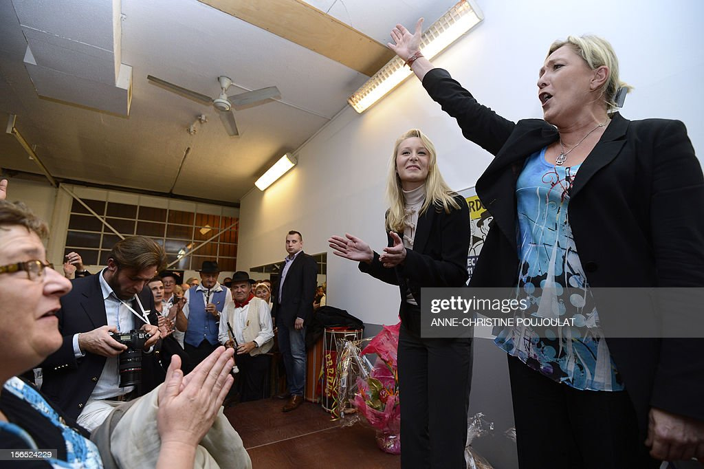 French far-right Front National (FN) MP Marion Marechal-Le Pen (L) and her aunt and party's president, Marine Le Pen, gestures during the inauguration of her office as deputy on November 16, 2012 in Carpentras, southeastern France. AFP PHOTO / ANNE-CHRISTINE POUJOULAT