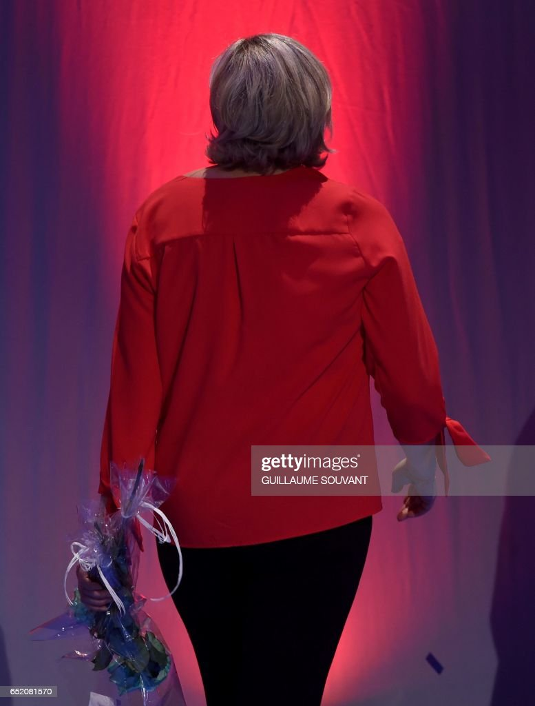 French far-right Front National (FN) party candidate for the presidential election Marine Le Pen leaves the stage after delivering a speech during a campaign rally on March 11, 2017 in Deols, central France. /