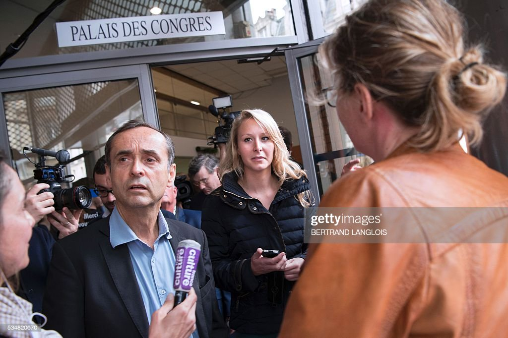 French far-right Front National (FN) party member of parliament Marion Marechal-Le Pen (C) and Beziers' mayor Robert Menard (L) leave the Palais des Congres in Beziers, southern France, on May 28, 2016 during 'Le Rendez-vous de Beziers' political meeting. Menard launched his own political movement 'Oz ta Droite'. / AFP / BERTRAND