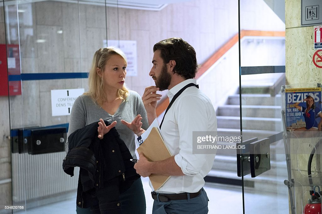 French far-right Front National (FN) party member of parliament Marion Marechal-Le Pen (L) speaks with former head of the youth organization of the French right-wing populist party Front National (FNJ) Julien Rochedy at the Palais des Congres in Beziers, southern France, on May 28, 2016 during 'Le Rendez-vous de Beziers' political meeting. Beziers' mayor Robert Menard launched his own political movement 'Oz ta Droite'. / AFP / BERTRAND