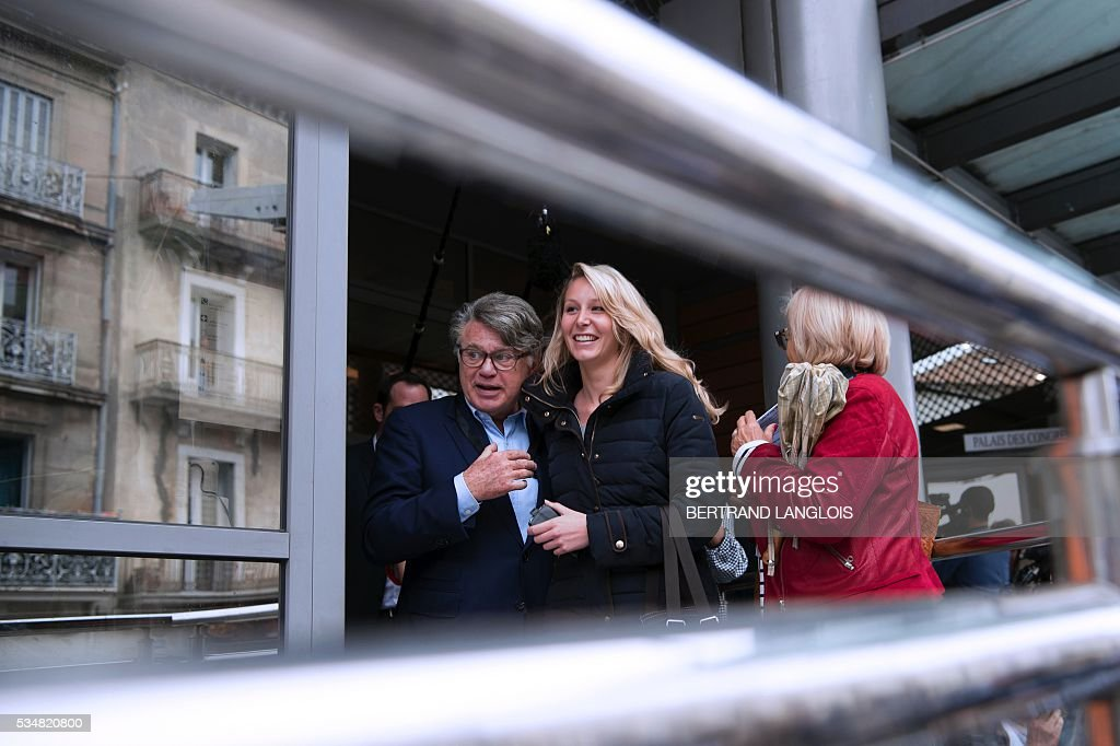 French far-right Front National (FN) party member of parliament Marion Marechal-Le Pen (C-R) and FN Member of Parliament Gilbert Collard (C-L) leave the Palais des Congres in Beziers, southern France, on May 28, 2016 during 'Le Rendez-vous de Beziers' political meeting. Beziers' mayor Robert Menard launched his own political movement 'Oz ta Droite'. / AFP / BERTRAND