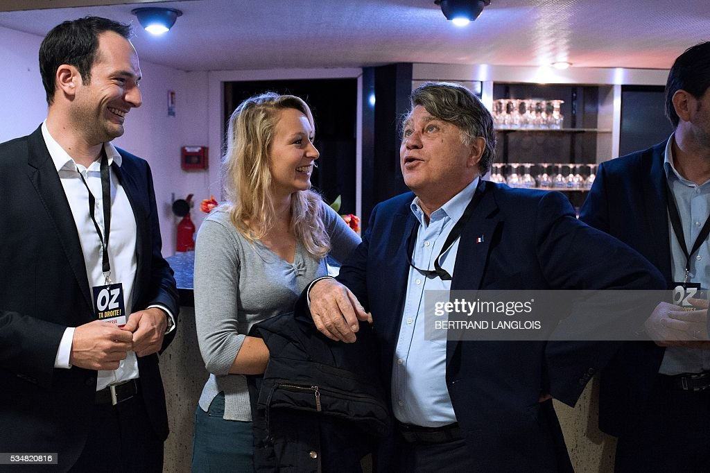 French far-right Front National (FN) party member of parliament Marion Marechal-Le Pen (2ndL) speaks with FN Member of Parliament Gilbert Collard at the Palais des Congres in Beziers, southern France, on May 28, 2016 during 'Le Rendez-vous de Beziers' political meeting. Beziers' mayor Robert Menard launched his own political movement 'Oz ta Droite'. / AFP / BERTRAND
