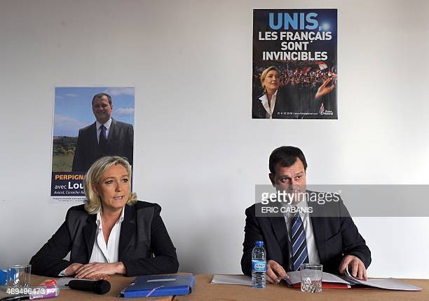 French farright Front National party president Marine Le Pen and FN candidate in Perpignan for the March 2014 mayoral elections Louis Aliot speak to...