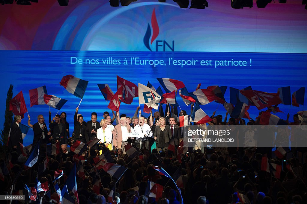 French far-right Front National (FN) party President Marine Le Pen and her father and FN honour president Jean-Marie Le Pen sing the national anthem as they acknowledge the audience after delivering a speech during the FN summer congress on September 15, 2013 in Marseille, southern France.