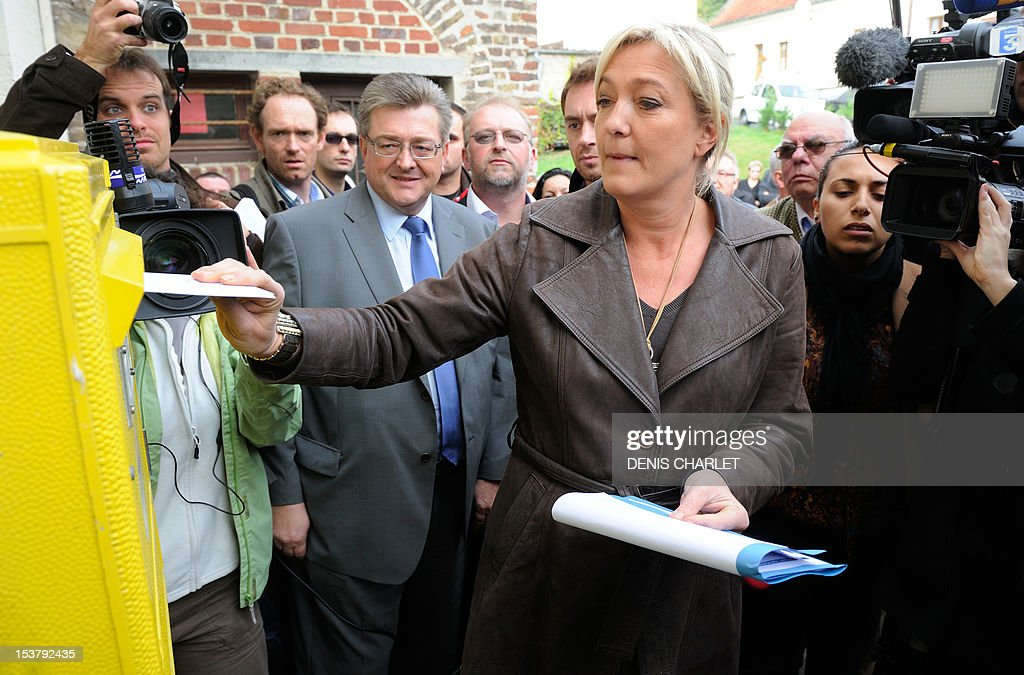 French far-right Front National (FN) party president Marine Le Pen (C) posts symbolically postcards addressed to the Elysee palace, on October 9, 2012 in the village of L'Etoile, northern France to mark its opposition to the Fiscal Stability Treaty and call for a referendum on the subject. AFP PHOTO / DENIS CHARLET