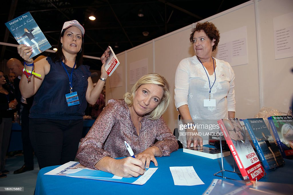 French far-right Front National (FN) party president Marine Le Pen (C) signs autographs as she attends the FN summer congress on September 14, 2013 in Marseille, southern France.