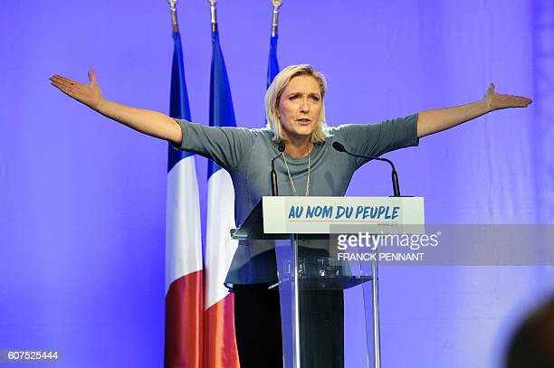 TOPSHOT French farright Front National party's President Marine Le Pen gestures as she delivers a speech on stage during the FN's summer congress in...