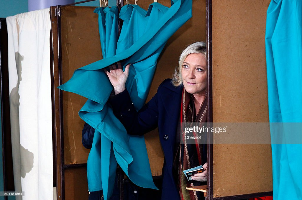 French far-right Front National (FN) party's President Marine Le Pen candidate for the regional election in the Nord-Pas-de-Calais-Picardie region leaves the polling booth to cast her ballot on December 13, 2015 in Henin-Beaumont, France. France is holding its second round of the regional elections.