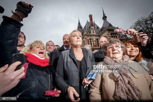 French farright Front National party's president Marine Le Pen stands with supporters on October 24 2014 during a visit in the city of Calais...